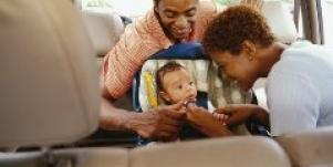 parents buckling a baby into a car seat