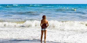 Girl standing facing water