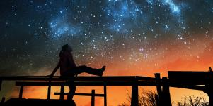 person sitting out under the stars