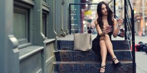 pretty woman on her phone sitting on city stoop