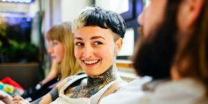smiling person with short hair and tattoos