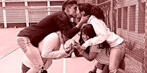 couple kissing with family