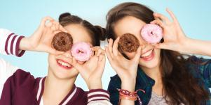 two girls holding donuts up to their eyes