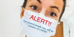 dr teresa dean wears a mask that says vaccinated people can still carry covid