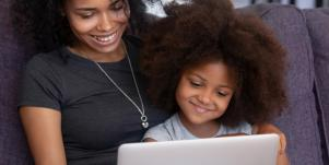 mom and young daughter looking at a laptop screen
