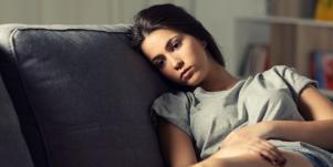sad woman on couch thinking