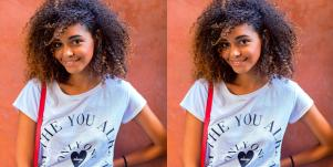 young Black woman smiles at the camera on an orange background
