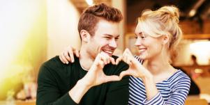 man and woman making a heart together with their hands