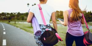 woman walking with gym bags