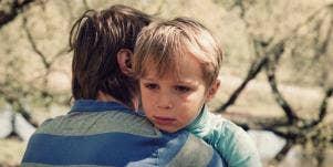 sad boy hugging father