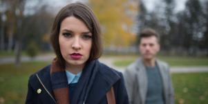 upset looking woman with man behind her