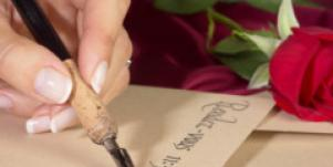 hand holding pen letter writing with red rose