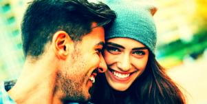 man with brown hair nuzzles the face of his girlfriend, romantically