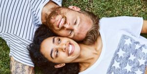 Man falling in love with woman laying down on grass