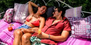 man and woman lounging on pink blanket smiling in the sun