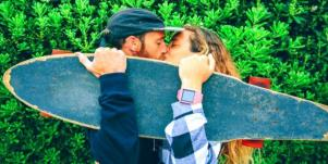 man and woman kissing and holding up skateboard