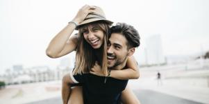 woman with hat smiling getting piggyback ride from man