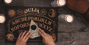 hands over a ouija board planchette