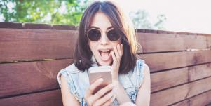 woman looking surprised at her phone