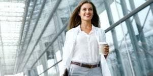 woman walking down a glass hallway holding coffee