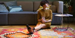 woman with short brown hair wearing a green dress sits on a patterned rug and looks toward a window