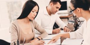 couple signing divorce papers with an attorney