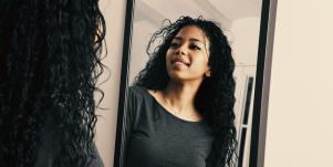 woman looking in the mirror to love herself again