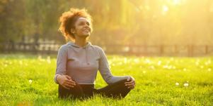 smiling woman meditating outside in the sun