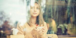woman drinking tea looking out window