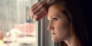 woman looking out the window thinking about negative feedback