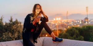 woman smiling sitting on ledge with phone in her hand