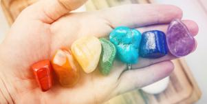 hand holding rainbow colored gemstones