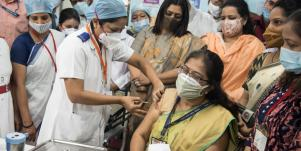 woman getting a vaccine in india while a crowd watches