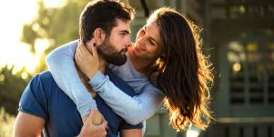 woman with arms around man's neck hugging from behind