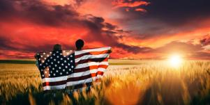 couple holding American flag watching sunset