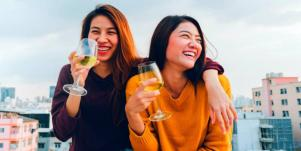 two women laughing and drinking