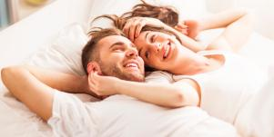 happy couple wearing white in bed