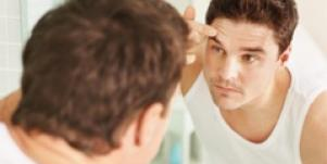 man primping in front of mirror