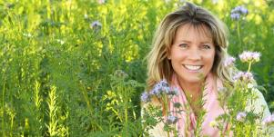 smiling woman surrounded by tall grass