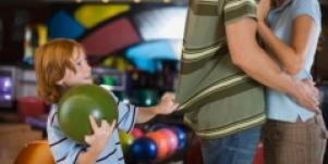 mom and dad kissing with child watching at bowling alley