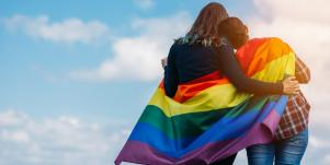 two women embracing under lgbt flag