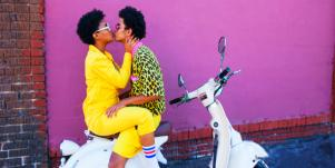 couple kissing on a scooter