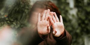 woman with hands up in front of face