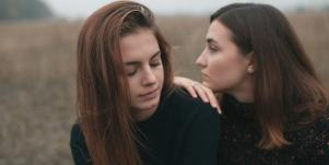 two friends leaning on each other