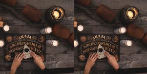 hands on planchette and ouija board