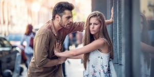 scared woman pushing angry man away