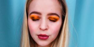blond woman orange eyeshadow blue background