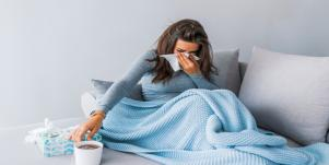 sick woman with tissues in bed
