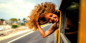woman with head out the window hair blowing in wind