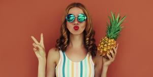 woman making peace sign duck face holding pineapple